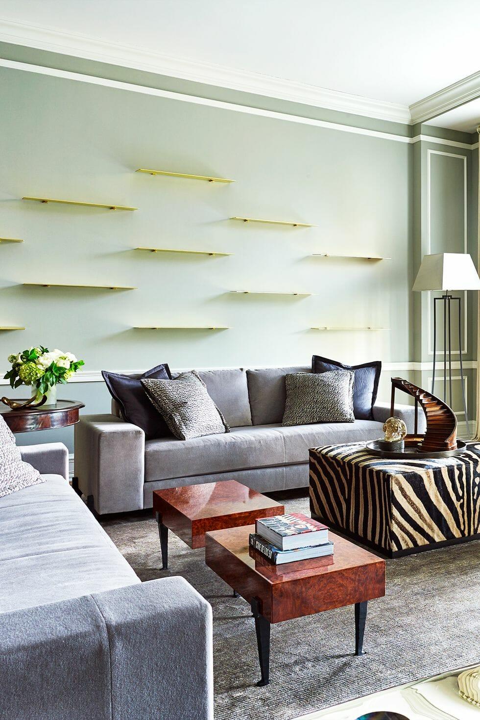 hình ảnh phòng khách hiện đại với sofa xám, bàn trà bọc vải họa tiết ngựa vằn, hệ kệ nổi gắn tường