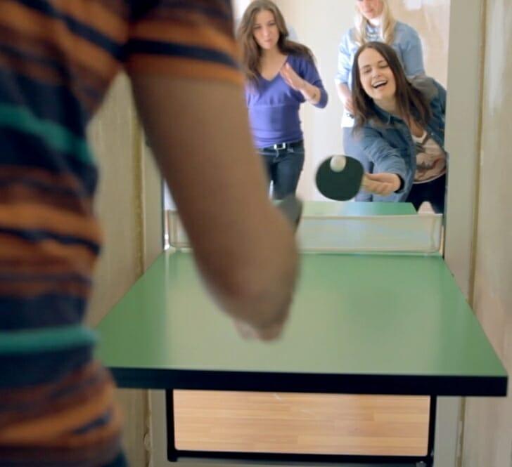 hình ảnh bàn bóng bàn độc đáo bắc ngang cửa, hai người phụ nữ đang chơi