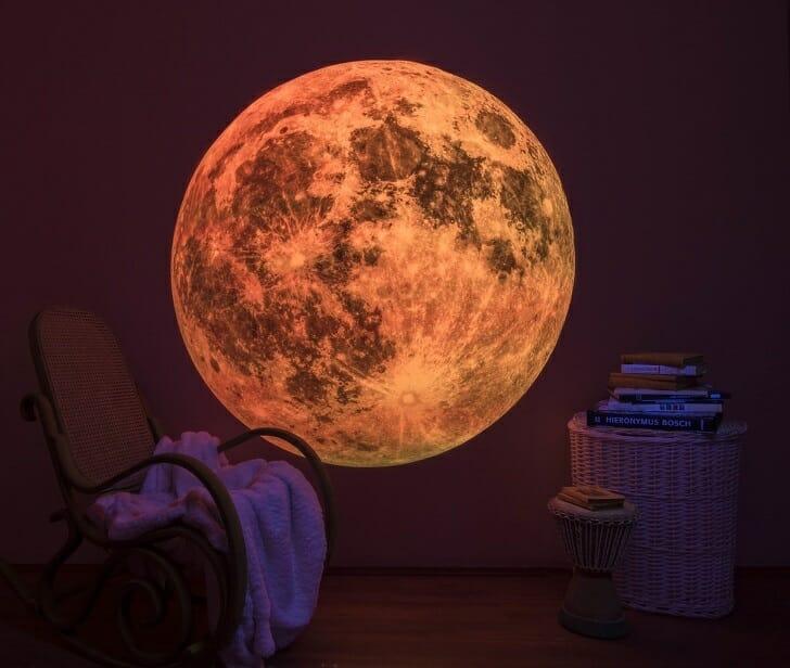 hình ảnh hình in mặt trăng phát sáng trên tường màu tím, cạnh đó là ghế ngồi thư giãn, bàn mây tre đan đặt chồng sách