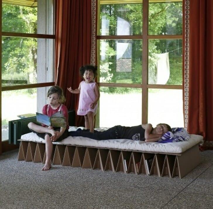hình ảnh các bé đang nằm, ngồi trên giường làm từ bìa cứng