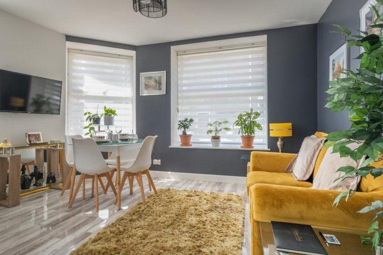 hình ảnh phòng khách liên thông khu bếp ăn với sofa màu vàng, đối diện là bộ bàn ăn nhỏ gọn, gạch giả đá lát sàn