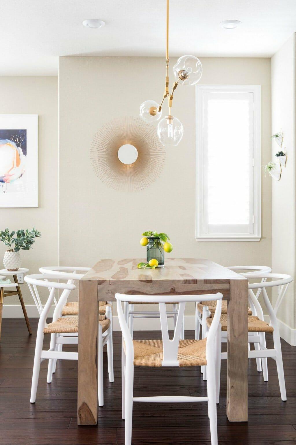 hình ảnh phòng ăn nhỏ phong cách bãi biển với bàn gỗ hình chữ nhật, ghế ngồi màu trắng, cây xanh tạo điểm nhấn