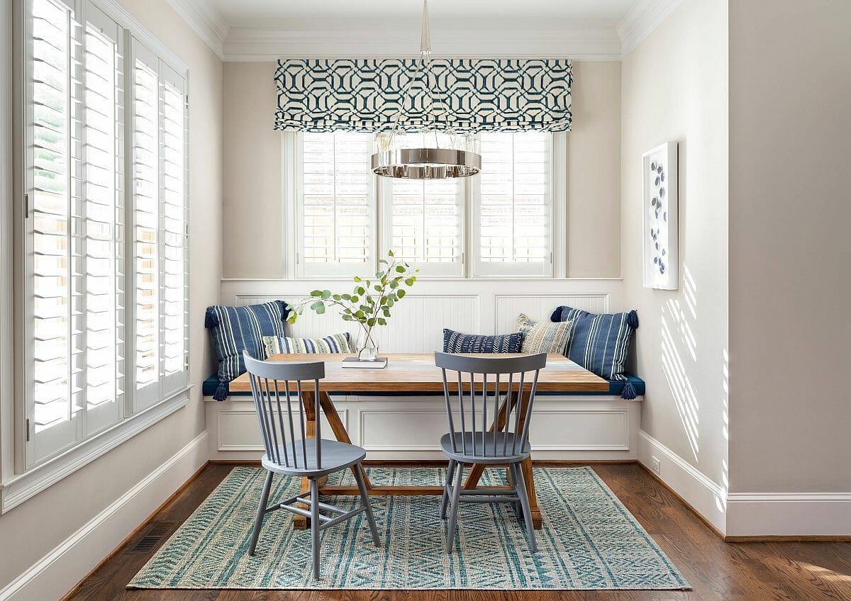hình ảnh phòng ăn nhỏ với bàn gỗ chữ nhật, ghế đôi màu xám khói, thảm trải và rèm cửa cùng tông, gối tựa kẻ sọc