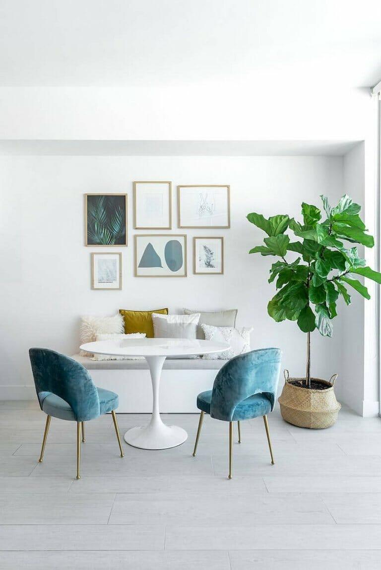 hình ảnh phòng ăn nhỏ với bàn tròn màu trắng, hai ghế bọc đệm màu xanh dương