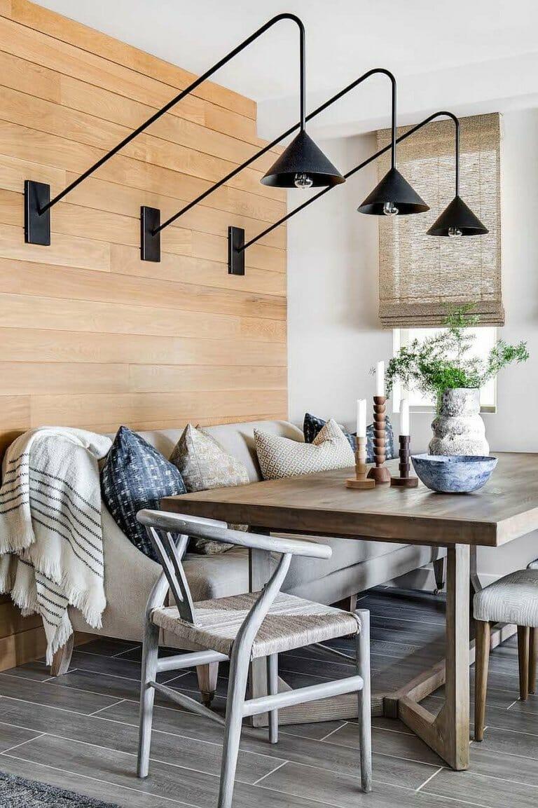 hình ảnh phòng ăn với bàn gỗ, ghế sofa xám, đèn treo tường màu đen độc đáo