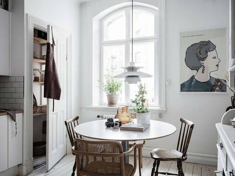 hình ảnh phòng ăn nhỏ màu trắng với tranh tường ấn tượng, bàn tròn, ghế mây, cửa sổ kính lớn, vài chậu cảnh trang trí