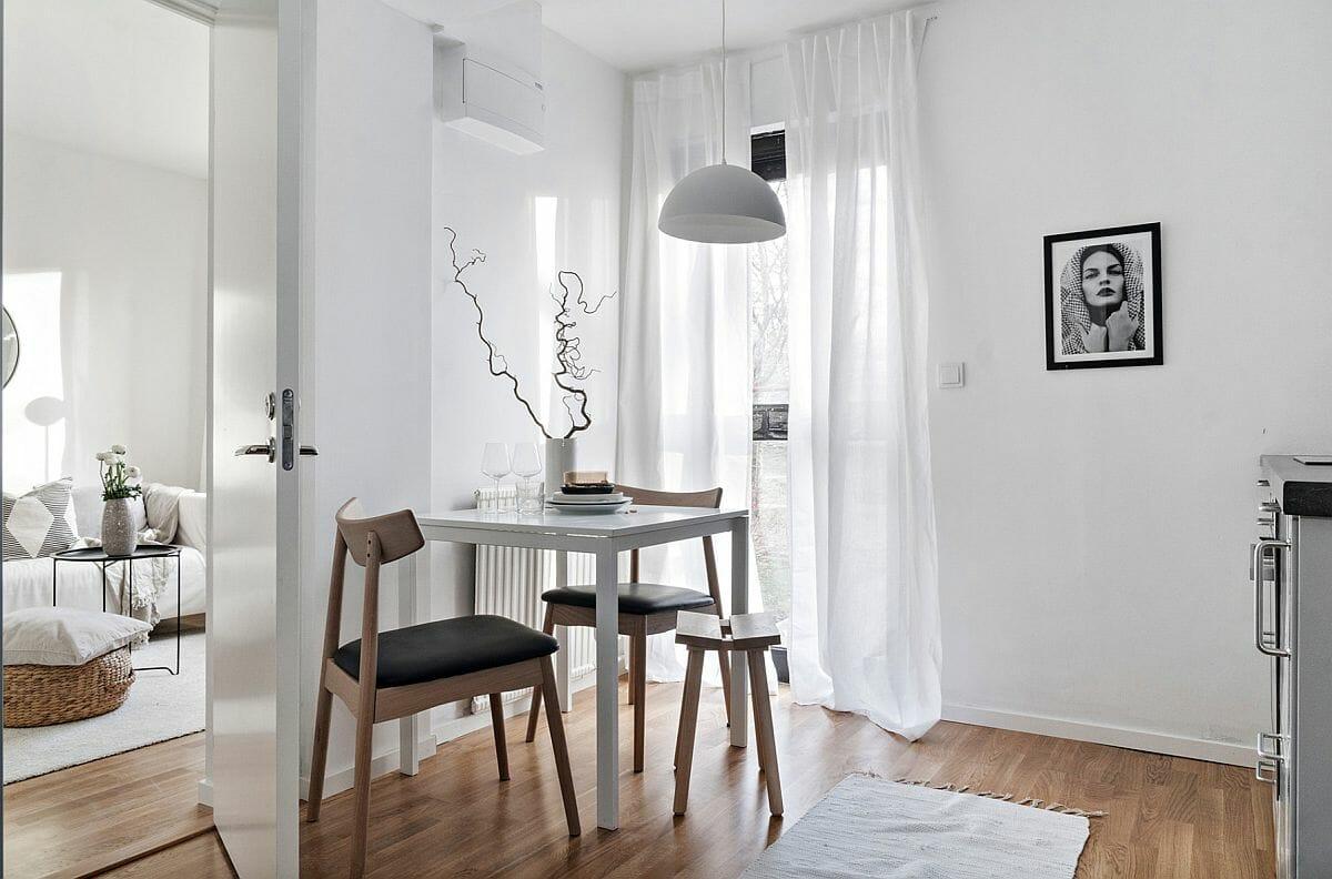 hình ảnh phòng ăn nhỏ màu trắng với bàn gỗ có thể gấp gọn, đèn thả màu trắng, cành cây trang trí