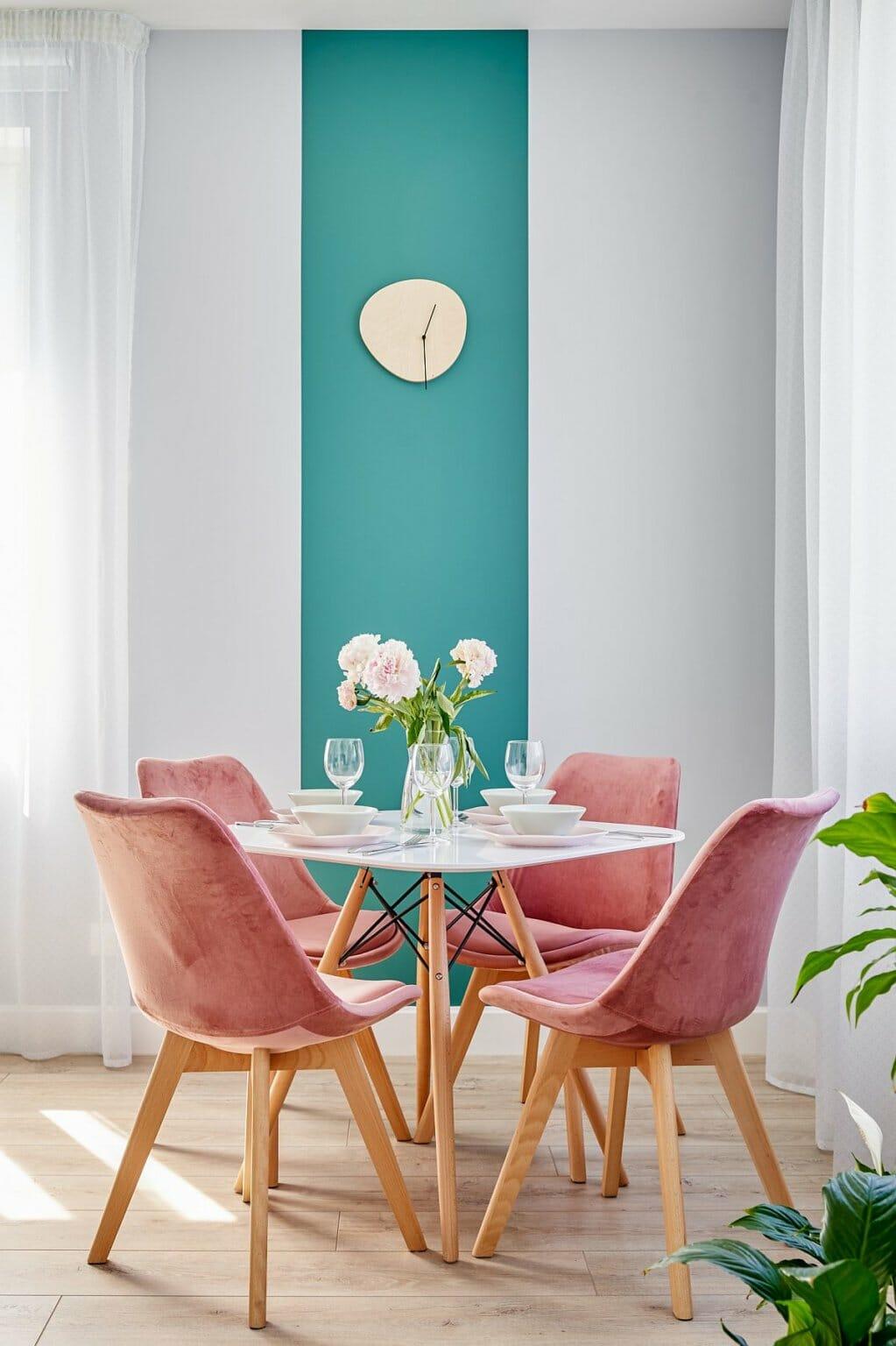 hình ảnh cận cảnh phòng ăn nhỏ với ghế ngồi màu hồng, mảng tường sơn xanh ngọc lam