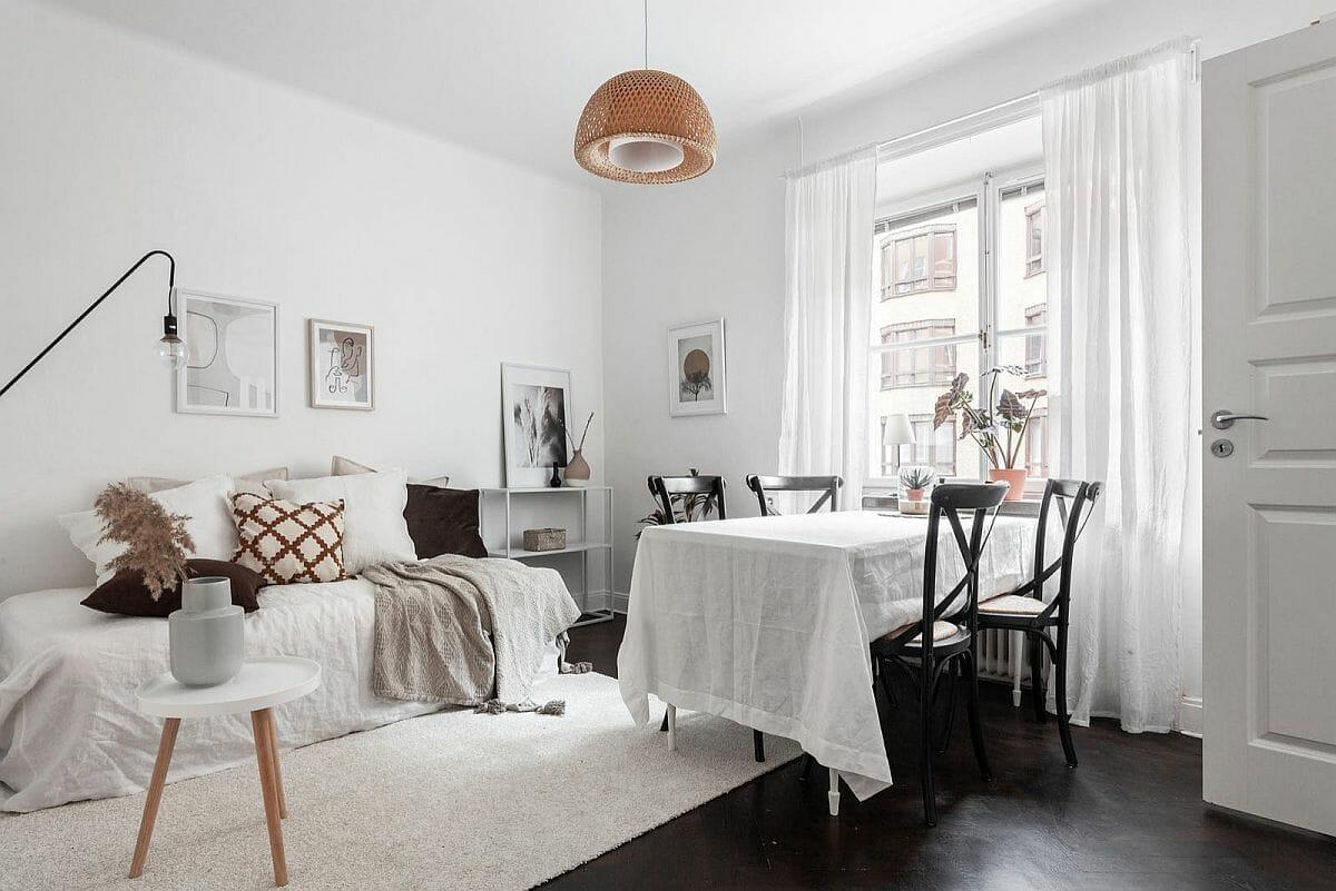 hình ảnh phòng ăn liền kề phòng khách trong căn hộ nhỏ màu trắng chủ đạo