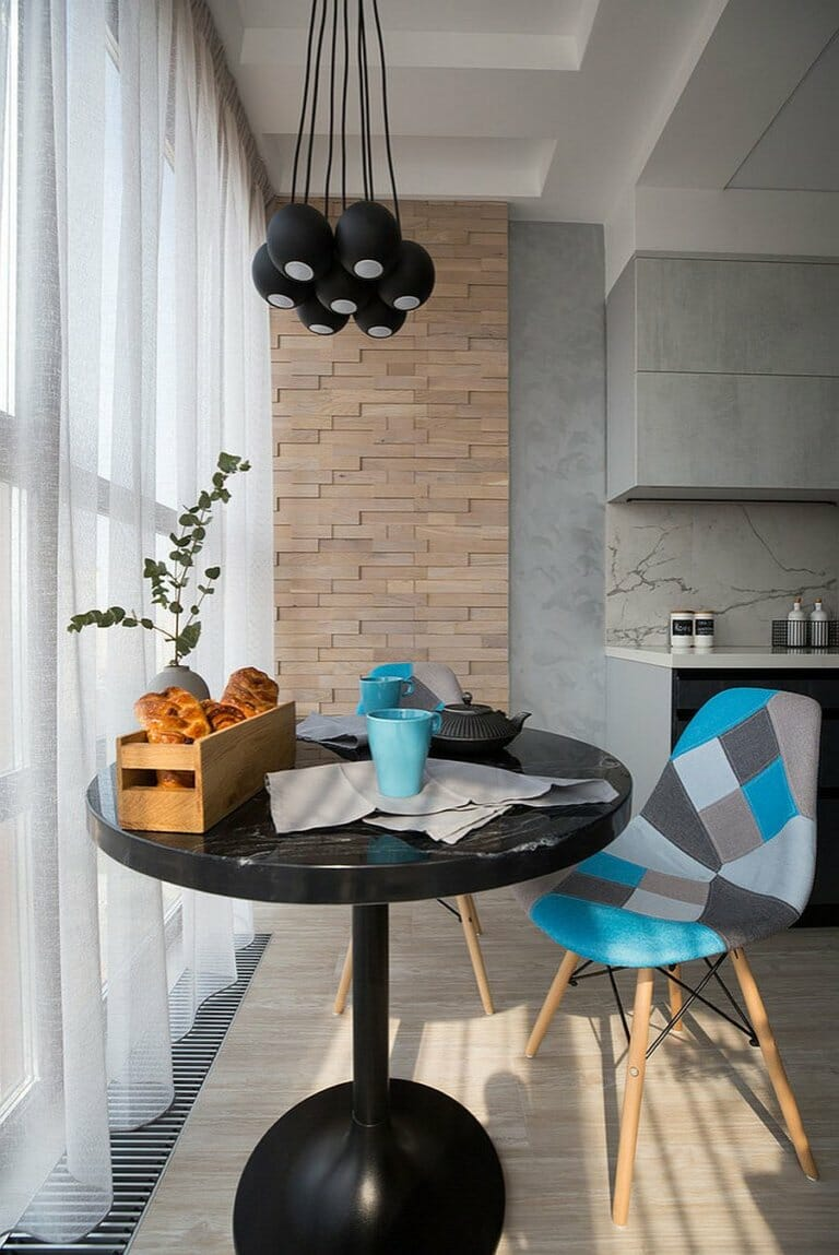hình ảnh cận cảnh bàn ăn hình tròn nhỏ màu đen, đèn thả cùng tông