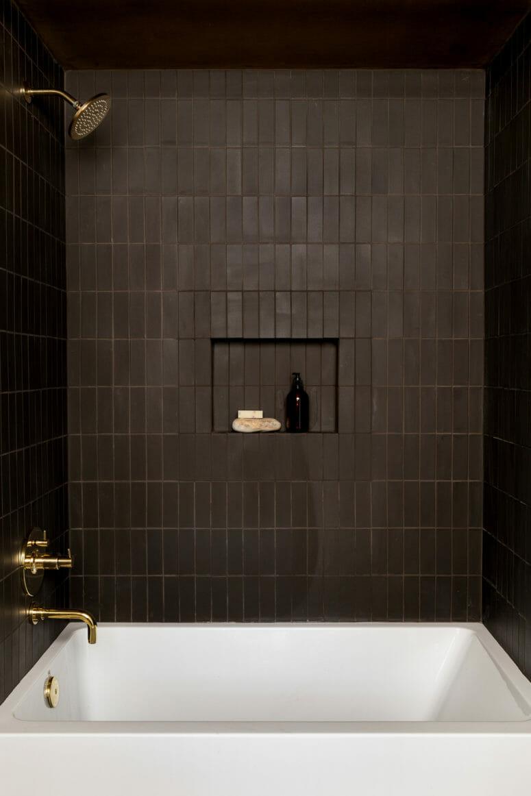hình ảnh phòng tắm màu nâu trầm chủ đạo với vòi sen, vòi rửa bằng đồng sáng bóng