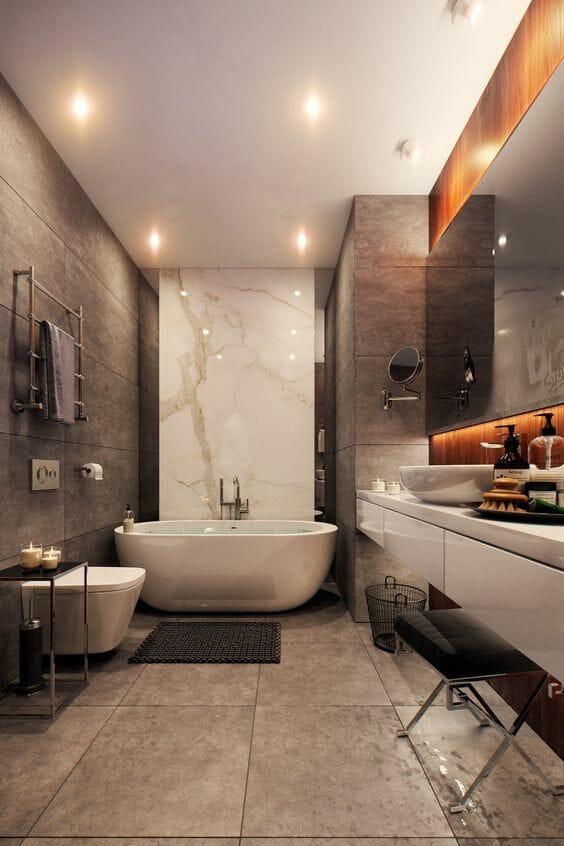 hình ảnh phòng tắm màu nâu nhạt với bồn tắm màu trắng, một mảng tường bằng đá cẩm thạch trắng, gương lớn gắn tường, đèn tường độc đáo