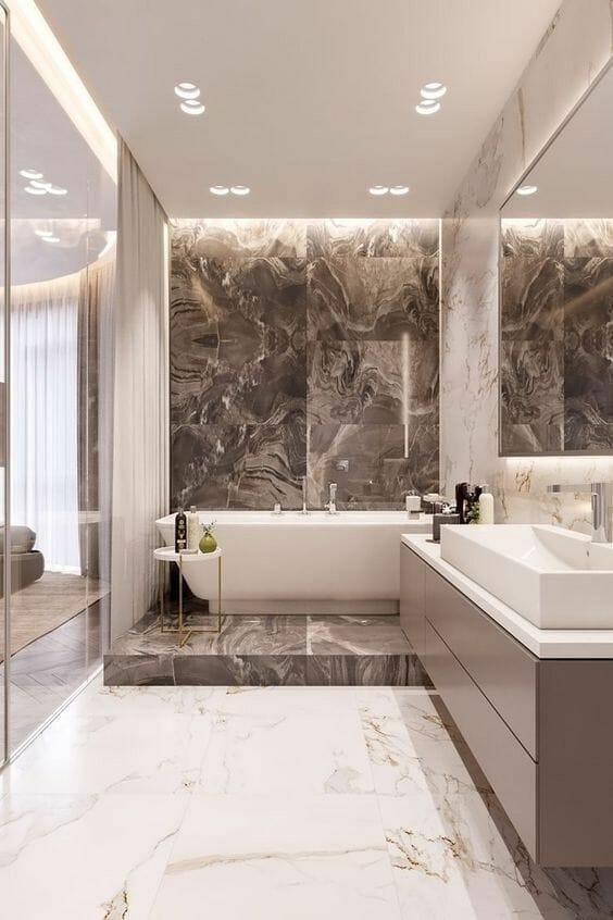 hình ảnh phòng tắm với sàn lát đá cẩm thạch màu nâu - trắng, bồn tắm đặt trên bục, bàn trang điểm dài