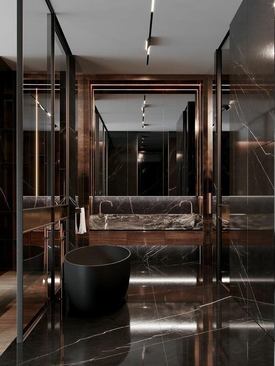 hình ảnh mẫu thiết kế phòng tắm cực ấn tượng với gạch lát đá cẩm thạch màu nâu chocolate, gương lớn, bồn tắm màu đen và ánh đèn LED ấm áp.