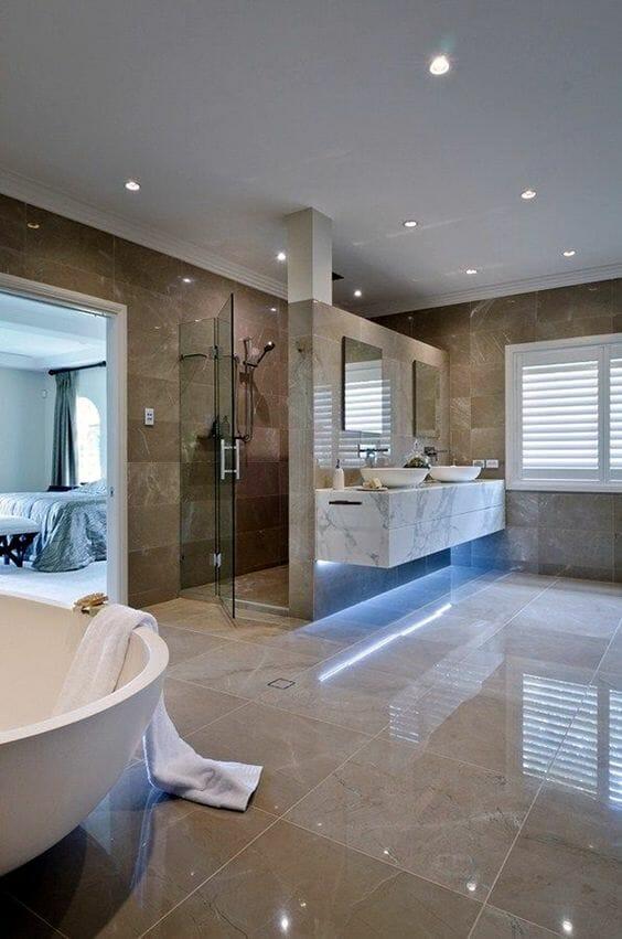 hình ảnh phòng tắm lớn hiện đại với gạch ốp lát màu nâu nhạt, đèn LED âm trần, bàn trang điểm lát đá cảm thạch