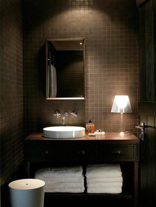 hình ảnh phòng tắm màu nâu chủ đạo vói gạch ốp lát màu nâu, bồn rửa mặt màu trắng, bên cạnh là đèn bàn sang trọng