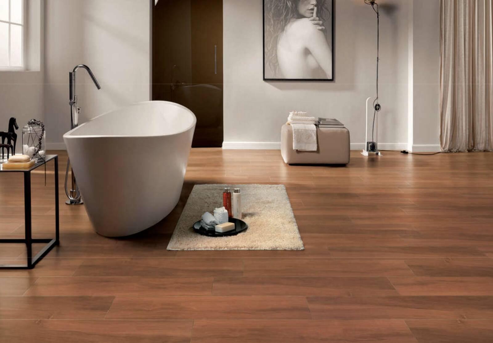 hình ảnh phòng tắm với sàn lát gạch vân gỗ, bồn tắm màu trắng đặt cạnh cửa sổ kính