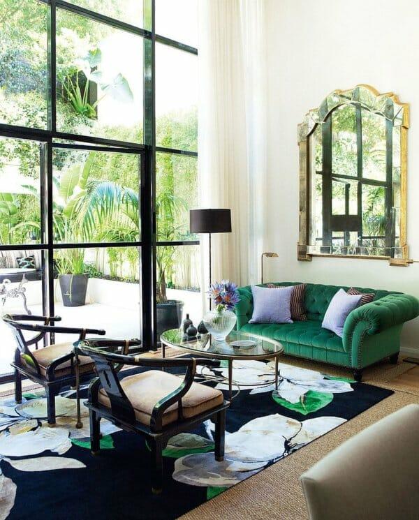Ghế đi văng màu xanh lá cây đậm và sang trọng tạo điểm nhấn tinh tế cho phòng khách tràn ngập ánh sáng này.
