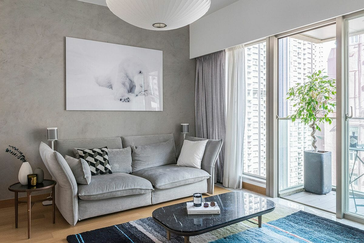 Phòng khách hiện đại của căn hộ ở Hồng Kông với điểm nhấn màu xám thanh lịch và ban công ngập tràn ánh sáng.