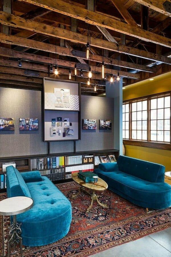 hình ảnh phòng khách với dầm gỗ lộ thiên, ghế sofa màu xanh ngọc, thảm trải thổ cẩm