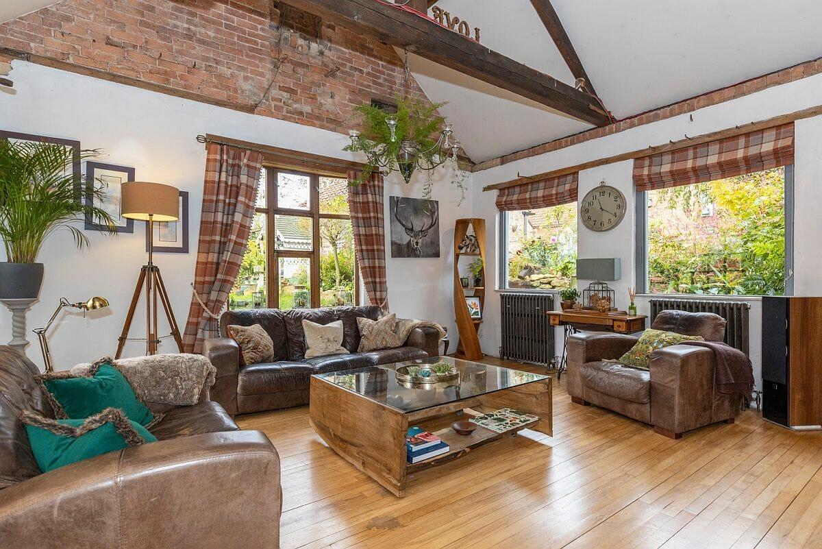 Phần tường gạch lộ ra ngoài mang đến một kết cấu hoàn toàn mới cho phòng khách màu trắng và gỗ chủ đạo.