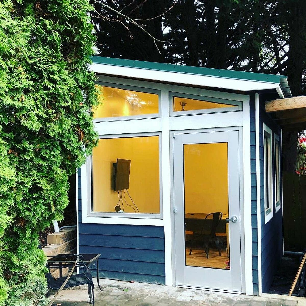Văn phòng nhỏ ở sân sau với cửa sổ kính lớn kết nối với thế giới bên ngoài.