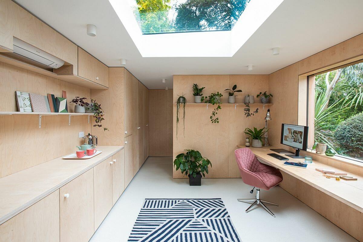 Cửa sổ lớn và cửa sổ trần cho phép ánh sáng tự nhiên ngập tràn văn phòng tại gia, kệ mở gắn tường đặt sách báo, chậu cây xanh