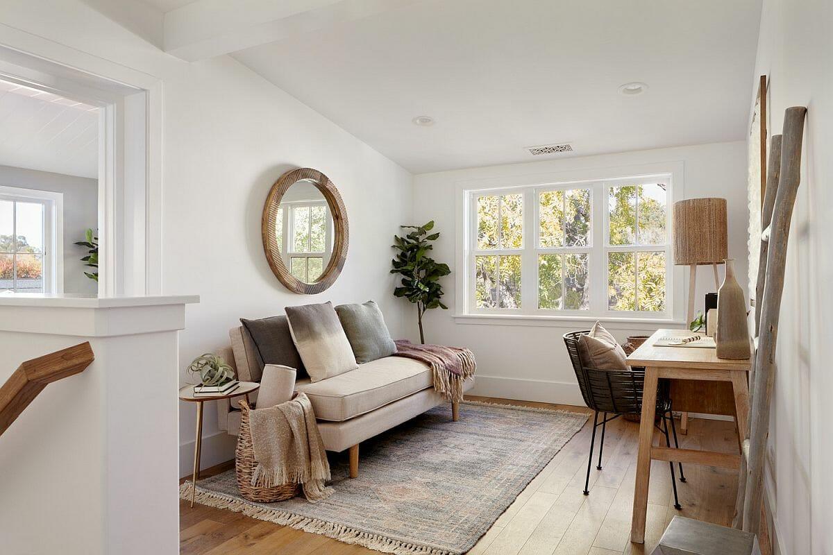 hình ảnh phòng khách màu trung tính chủ đạo, gương tròn treo tường, bàn làm việc đối diện ghế sofa
