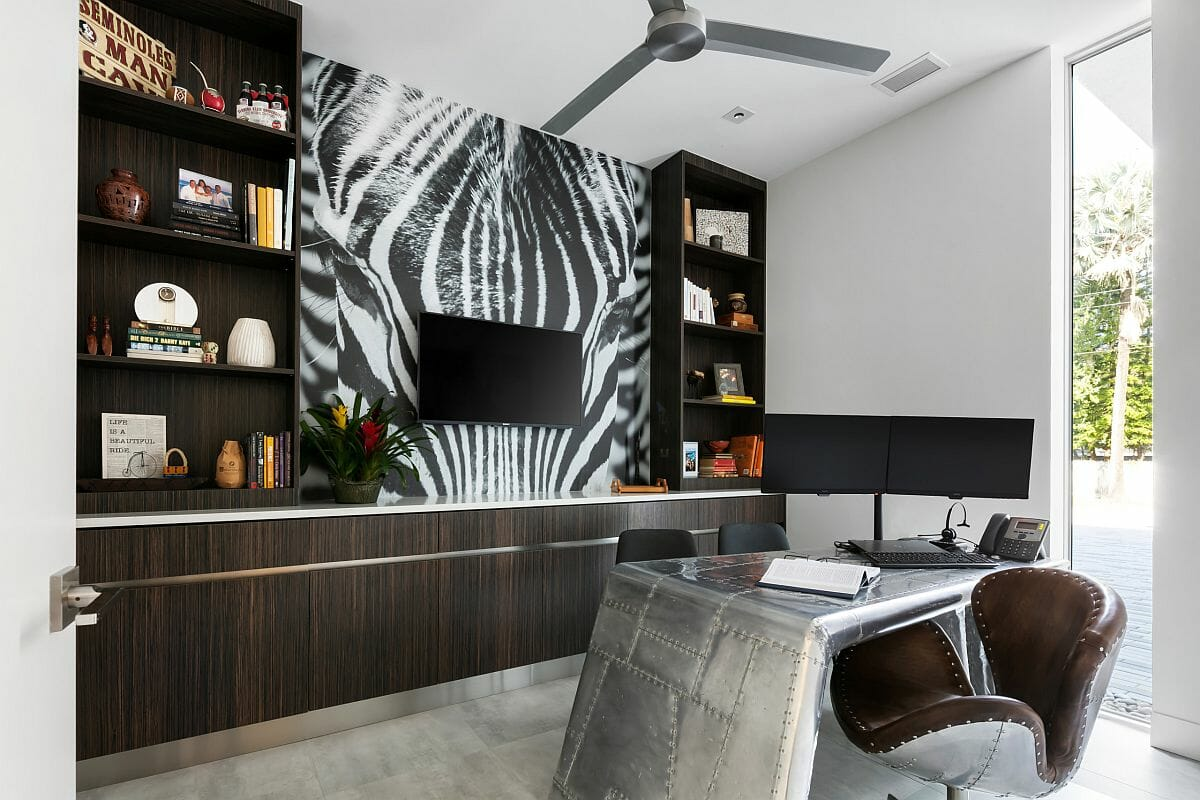 hình ảnh phòng làm việc với bàn ghế da màu xám, kệ gỗ sẫm màu, tranh tường trừu tượng