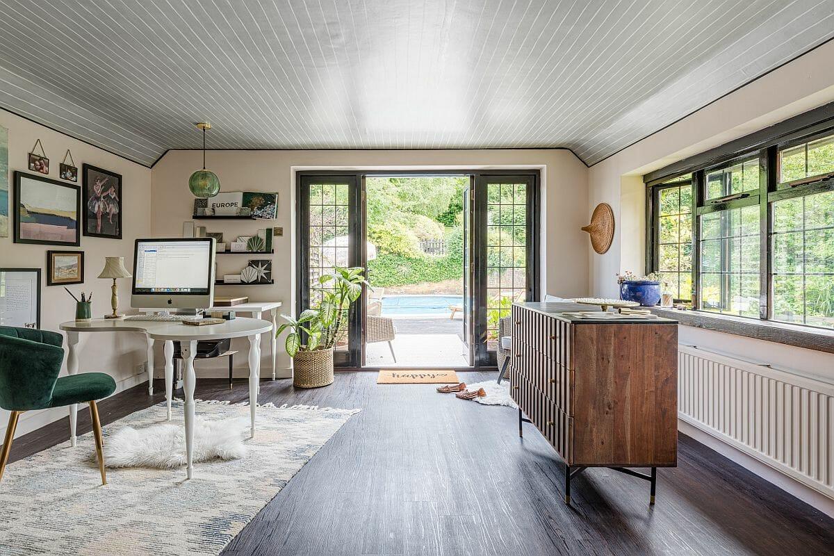 Hệ cửa kính trong suốt mang đến phông nền màu xanh thiên nhiên dịu mát cho không gian làm việc tại nhà của bạn.