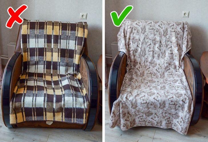hình ảnh cận cảnh chăn len kẻ sọc đen vàng và chăn họa tiết bướm phủ trên ghế bành