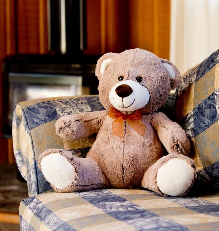 hình ảnh cận cảnh chú gấu bông lớn đặt trên ghế sofa họa tiết