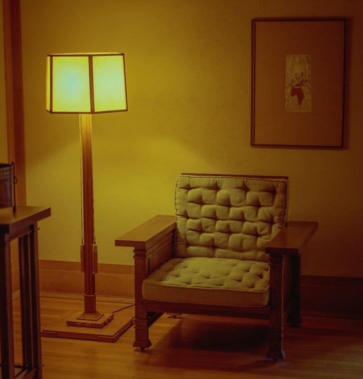 hình ảnh cận cảnh đèn sàn với ánh sáng vàng đặt cạnh ghế tựa