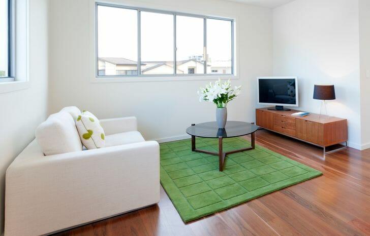 hình ảnh phòng khách với tường và trần sơn trắng, cửa sổ kính lớn, sofa trắng, bàn trà tròn, kệ tivi bằng gỗ, thảm trải sàn màu xanh lá cây