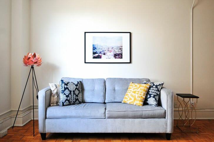 hình ảnh phòng khách với sofa màu xanh sáng, tranh treo tường, đèn sàn độc đáo