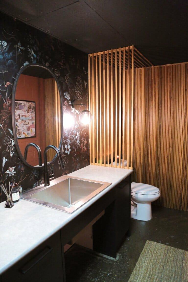 hình ảnh phòng tắm với giấy dán tường họa tiết hoa lá tối màu, gương hình elip, lam gỗ màu sáng