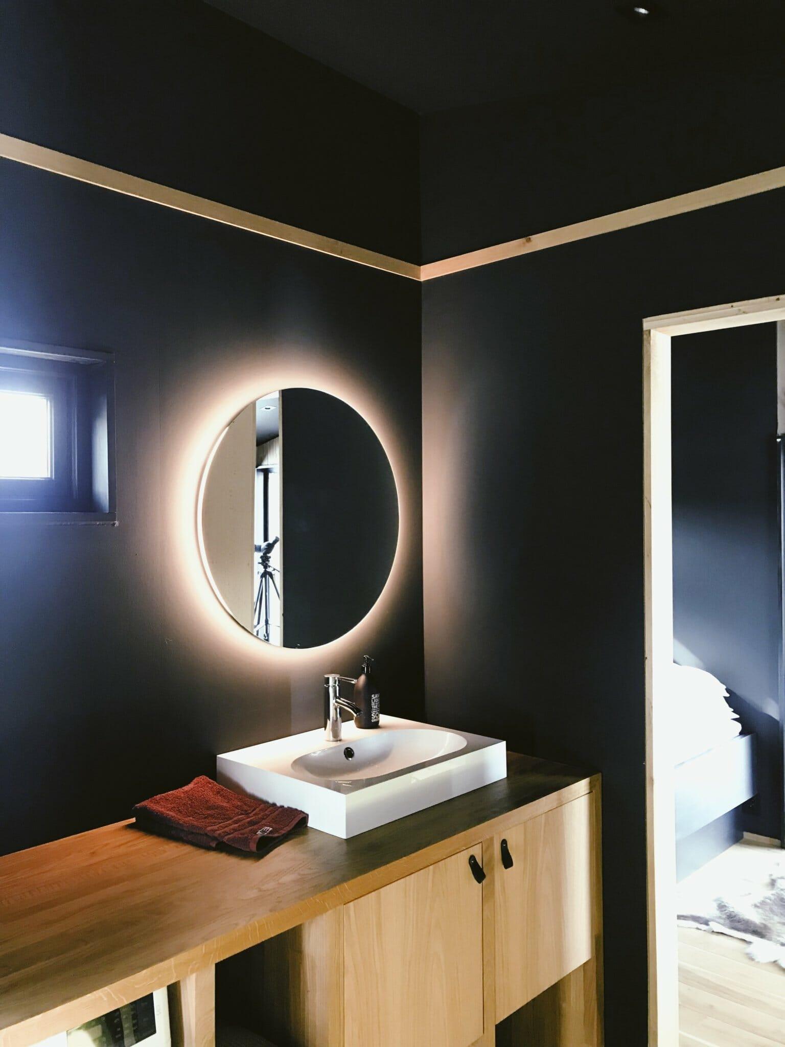 hình ảnh một góc phòng tắm với tường sơn màu xanh than, gương tròn kết hợp đèn LED, bồn rửa sứ trắng hình chữ nhật