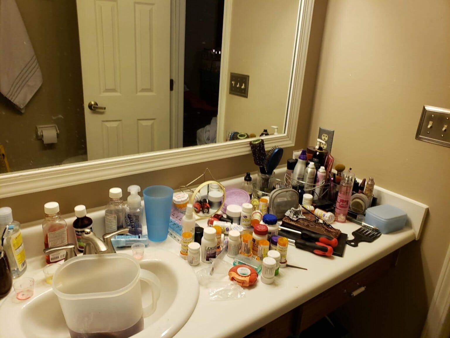 hình ảnh bệ bồn rửa mặt phòng tắm với la liệt vật dụng cá nhân như sữa dưỡng, sữa tắm, dầu gội...