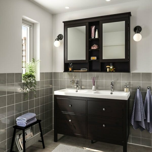 hình ảnh phòng tắm với gạch ốp tường màu xám, bồn rửa sứ trắng, gương với đèn tròn màu trắng đối xứng hai bên, cửa sổ kính