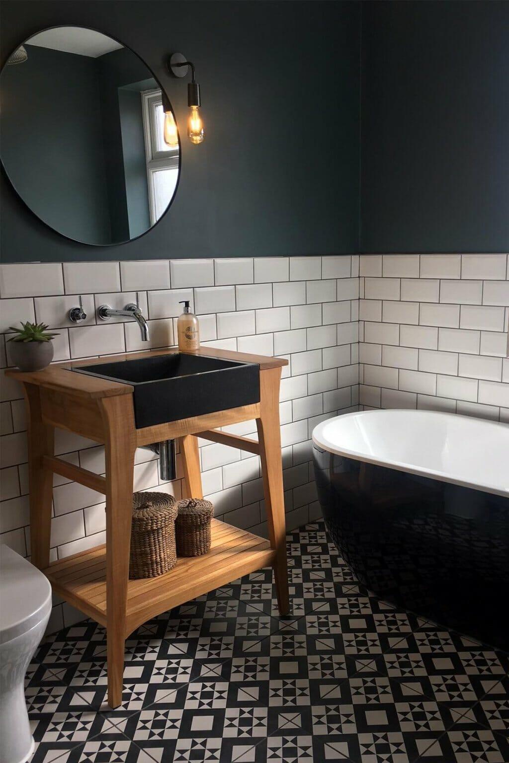 hình ảnh một góc phòng tắm với bồn tắm màu xanh than, gạch thẻ ốp tường màu trắng, đèn sợi đốt treo cạnh gương, kệ gỗ đựng đồ