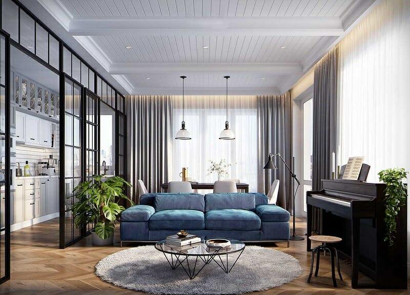 hình ảnh phòng khách rộng rãi, thoáng sáng với bộ ghế sofa màu xanh lam, đèn thả trần cổ điển, đàn piano, bàn trà và thảm trải tròn mềm mại