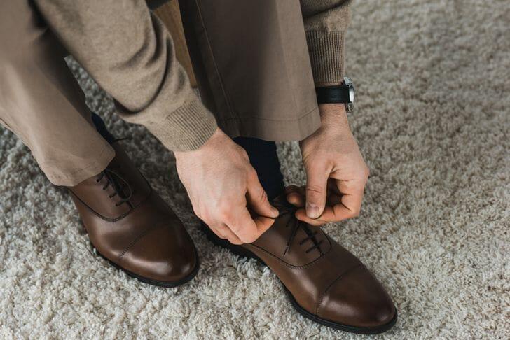 hình ảnh cận cảnh người đàn ông đang cúi xuống buộc dây giày màu nâu, đặt trên thảm lông màu be