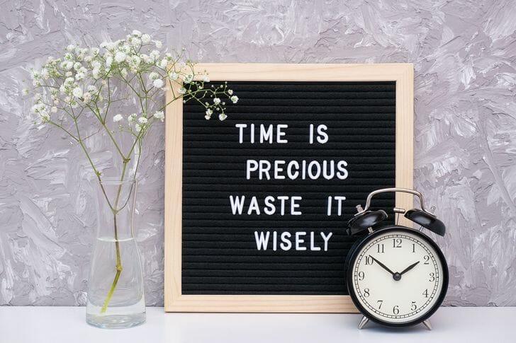 hình ảnh cận cảnh tường nhà với câu trích dẫn in trên khung đen, hoa màu trắng, đồng hồ để bàn